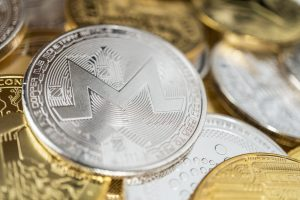 Close-Up of Monero Physical Coin On Stack of Many Other Cryptocurrencies