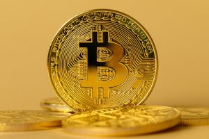 Closeup of gold bitcoin on yellow backgound